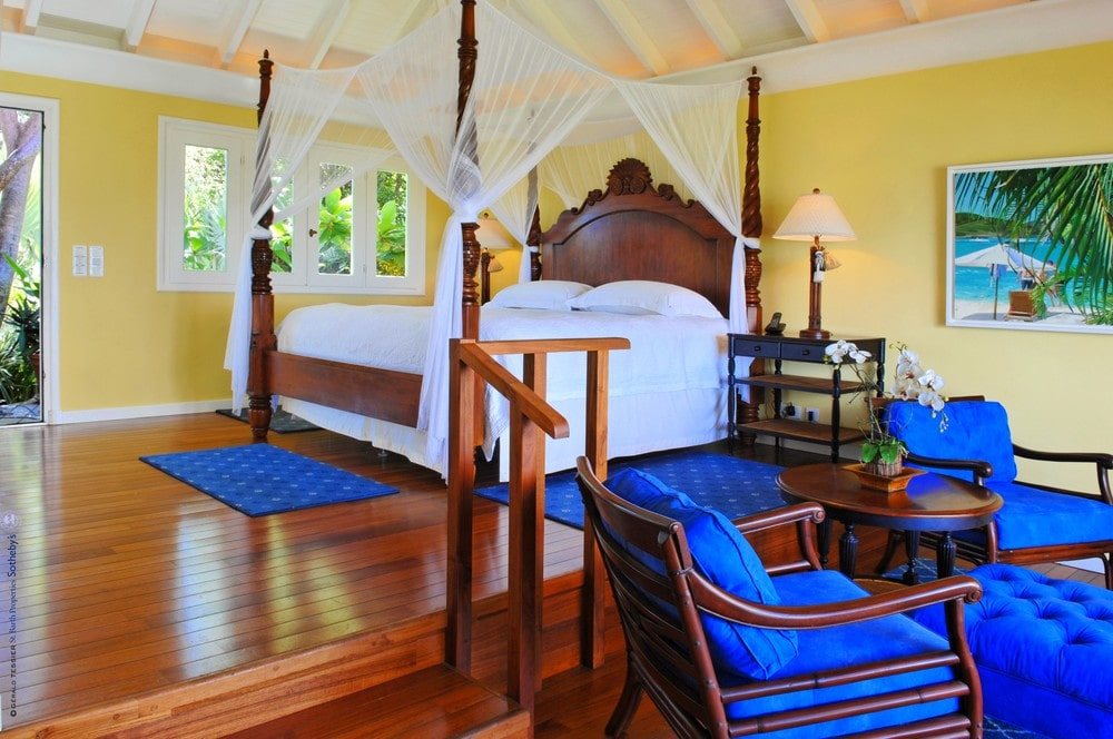 This other look at the bedroom shows the blue area rugs surrounding the wooden bed that matches with the cushions of the wooden armchairs of the sitting area. Image courtesy of Toptenrealestatedeals.com.