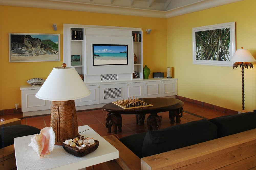 The family room has a wooden sofa set to match the wooden coffee table across from the large white structure that has built-in cabinets, shelves and wall-mounted TV. Image courtesy of Toptenrealestatedeals.com.