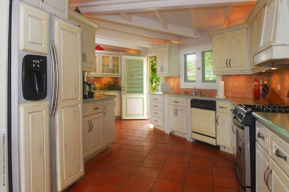 The kitchen has terracotta flooring tiles that complement the beige cabinetry that line the walls. Image courtesy of Toptenrealestatedeals.com.