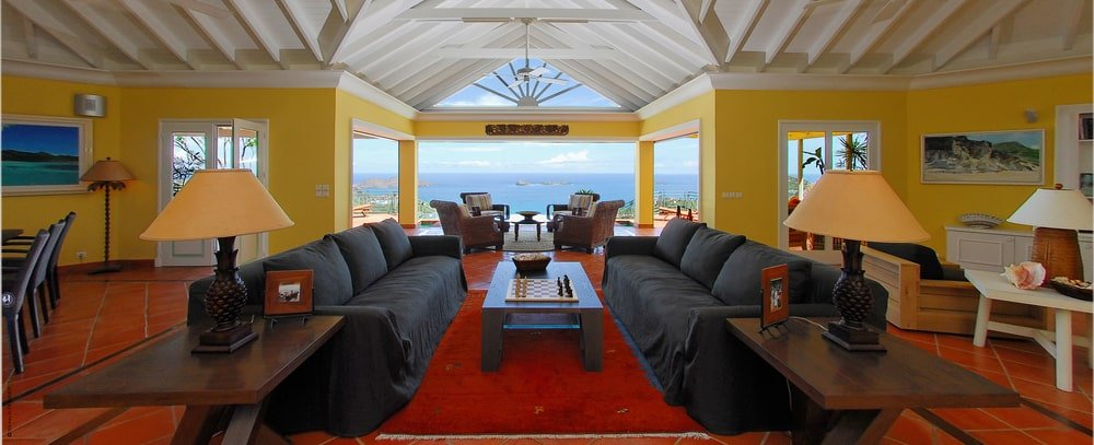 This is the bright and spacious living room with a couple of dark-toned couches that stand out against the red carpeted floor and the beige walls. Image courtesy of Toptenrealestatedeals.com.