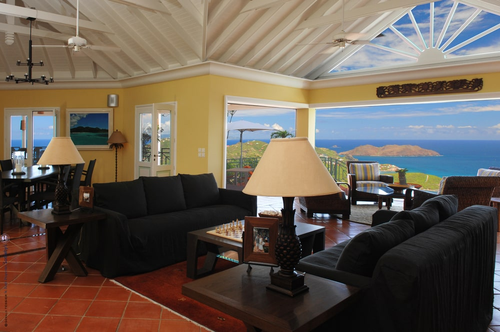 The living room has bright beige walls that are complemented by the tall white ceiling and the natural lights coming from the wide glass windows. Image courtesy of Toptenrealestatedeals.com.