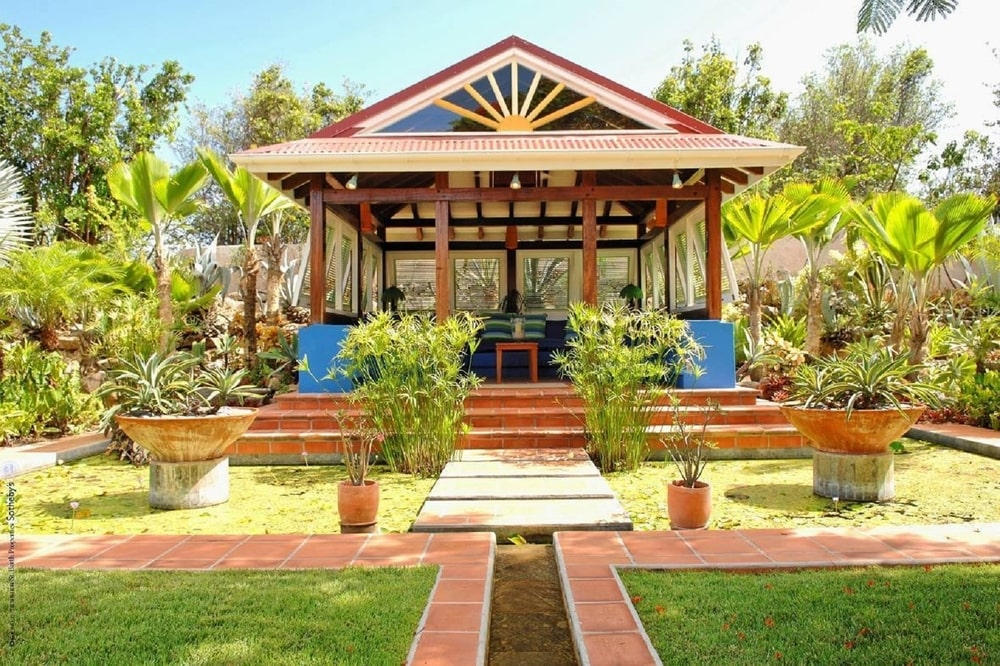 This is a look at the covered patio on the other side of the property. This is adorned with terracotta walkways, steps and potted plants that contrast the surrounding trees and shrubs. Image courtesy of Toptenrealestatedeals.com.