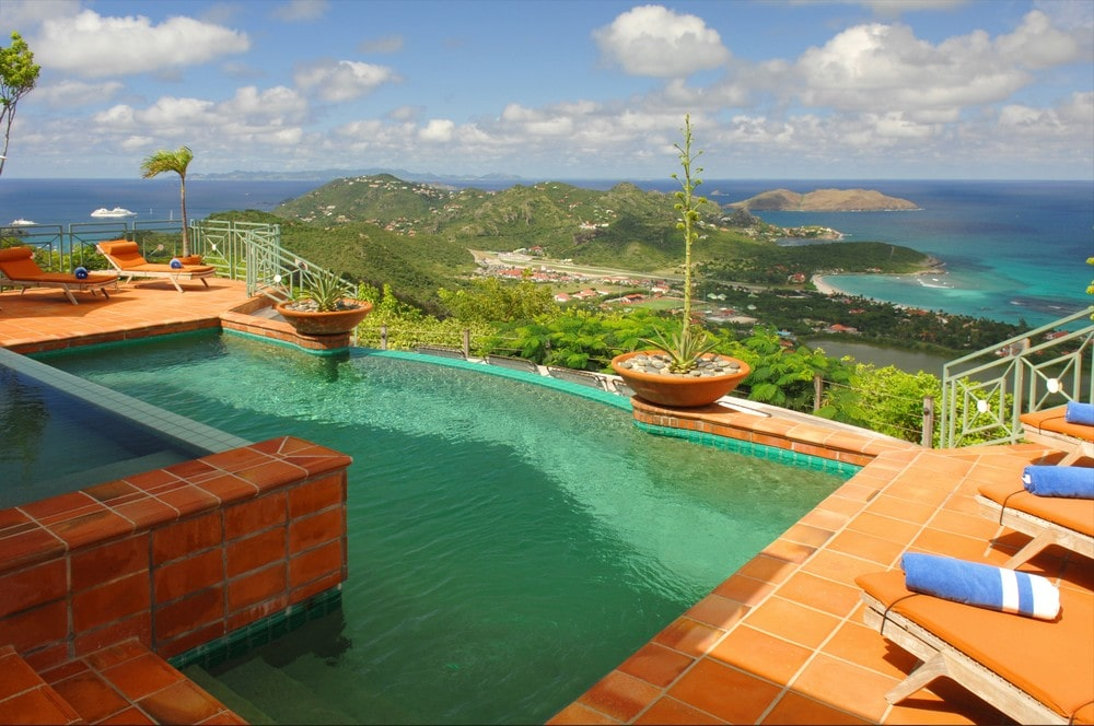This is the pool surrounded by terracotta tiles and matching potted plants to bring out the blue of the pool. Image courtesy of Toptenrealestatedeals.com.