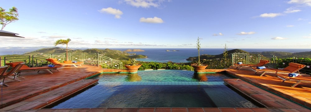 This is a look at the whole pool adorned with potted plants and the sweeping view of the ocean. Image courtesy of Toptenrealestatedeals.com.