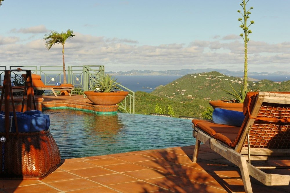 This is a look at the side of the pool fitted with an outdoor lawn chair to better enjoy the view of the ocean. Image courtesy of Toptenrealestatedeals.com.