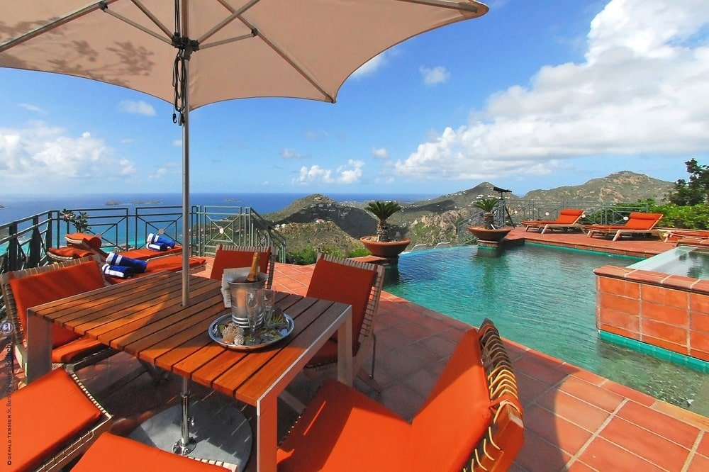 This is a look at the side of the pool fitted with an outdoor dining set under a large umbrella. Image courtesy of Toptenrealestatedeals.com.