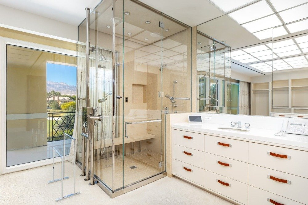 A look at the bathroom's walk-in shower booth with a white sink counter on the side. Image courtesy of Toptenrealestatedeals.com.