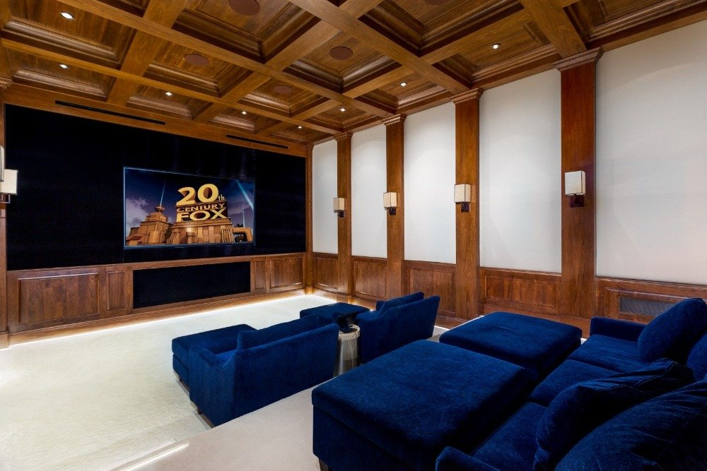 Home theater with elegant blue velvet seats facing the widescreen TV, surrounded by brown walls and ceiling. Image courtesy of Toptenrealestatedeals.com.