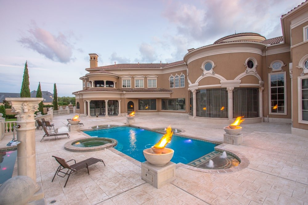 This is a view of the back of the house from the vantage of the poolside area. This pool is surrounded by decorative landscaping and beige stone walkways that match the exterior walls of the house. Image courtesy of Toptenrealestatedeals.com.