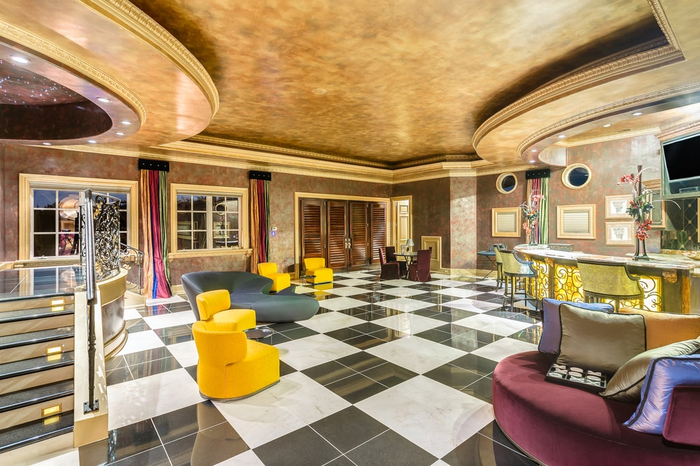 This is the bar and lounge area with a black and white checkered floor that makes the yellow tones of the chair and bar stand out. Image courtesy of Toptenrealestatedeals.com.
