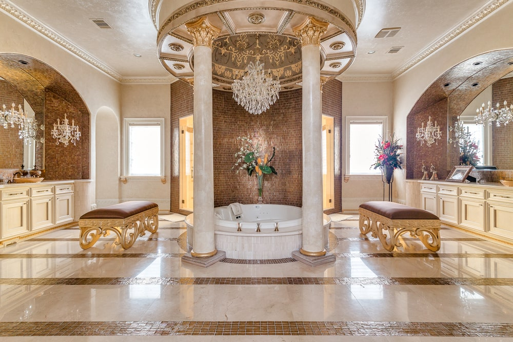 The bathroom has a bathtub in the middle under a large alcove adorned with tall pillars and a crystal chandelier. This is flanked by vanities on both sides. Image courtesy of Toptenrealestatedeals.com.