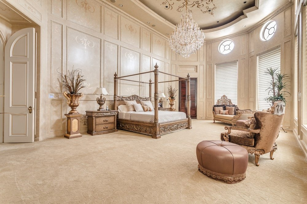 This is the spacious and airy primary bedroom with a four-poster bed that matches the hue of the surrounding bedside drawers, armchairs and cushioned ottoman. These stand out against the beige tone of the floor, walls and ceiling. Image courtesy of Toptenrealestatedeals.com.
