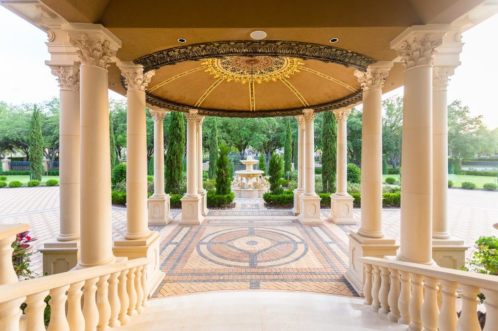 This is the main entrance of the mansion from the vantage of the main door. You can see here that there is a drop-off area supported by multiple pillars and a fountain on the far side. Image courtesy of Toptenrealestatedeals.com.