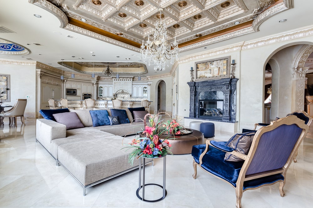 The family room has a large light gray L-shaped sectional sofa warmed by a fireplace embedded into the wall. Image courtesy of Toptenrealestatedeals.com.