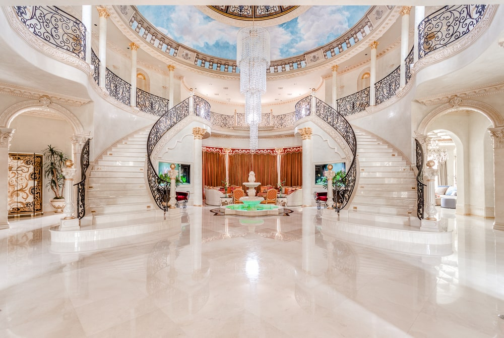 Upon entry of the house, you are welcomed by this massive foyer with beige tones and large circular tall ceiling. Image courtesy of Toptenrealestatedeals.com.