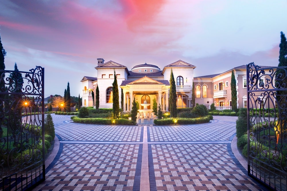 This is the front view of the palace-like mansion surrounded by well-manicured shrubs and trees and complemented by the outdoor lights. Here you can see the main entrance adorned with a fountain.