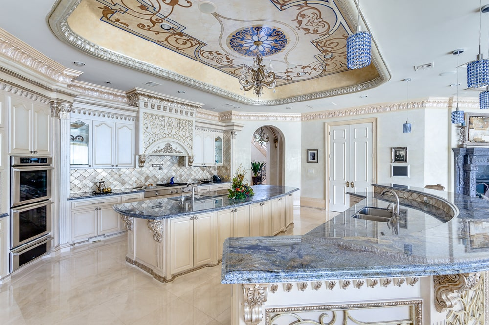 The kitchen has two kitchen islands with beige tones on the cabinetry under a tray ceiling with intricate details. Image courtesy of Toptenrealestatedeals.com.