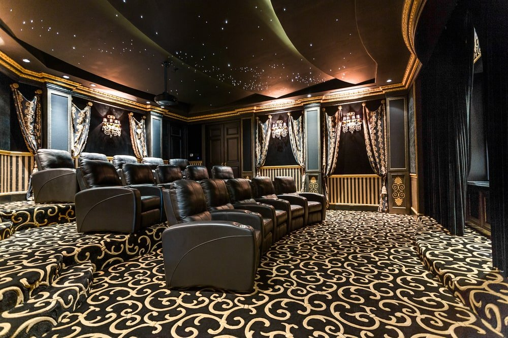 This is the large theater room with rows of ascending leather theater chairs facing the screen. These are then complemented by the patterned carpet. Image courtesy of Toptenrealestatedeals.com.