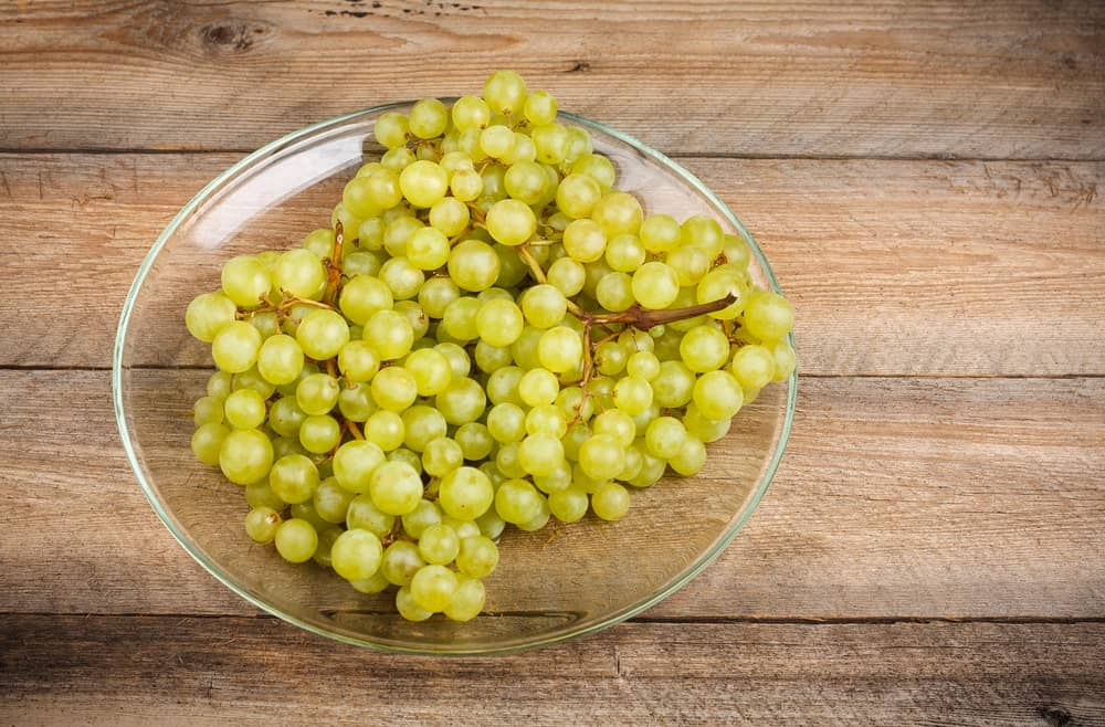 Sultana grapes in a glass plate over a wood plank table.