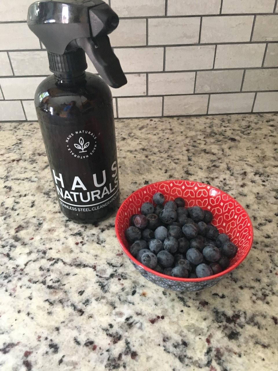 A bowl of summer berries beside a Haus Naturals bottle on a kitchen countertop.
