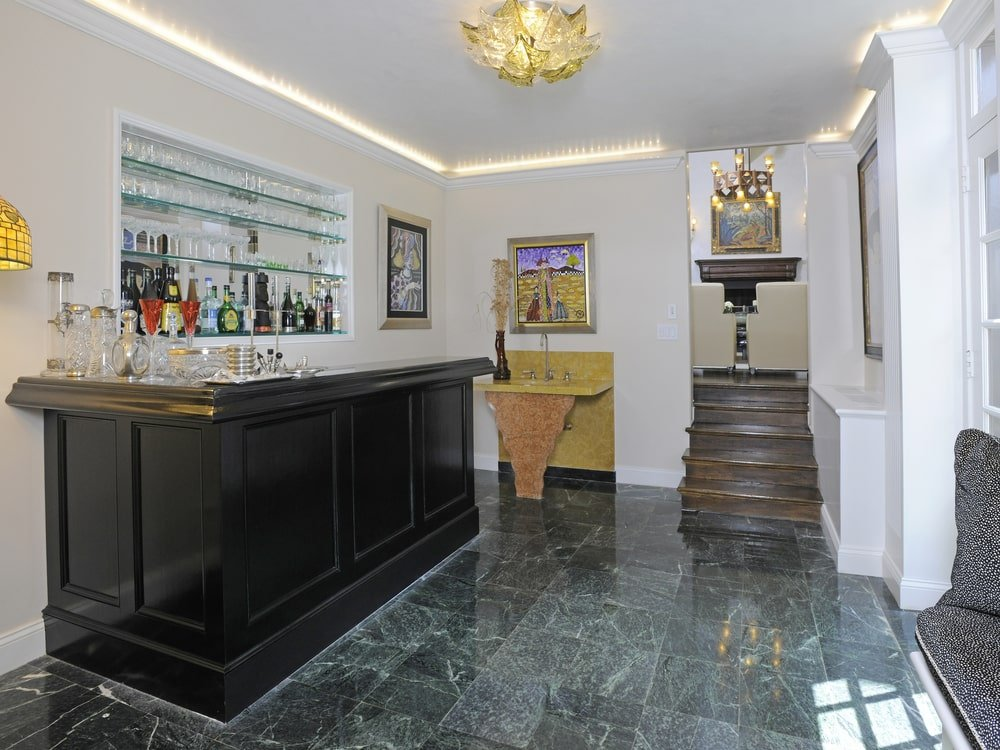 This is a look at the bar with a dark wooden counter and embedded glass shelves for liquor storage. Image courtesy of Toptenrealestatedeals.com.