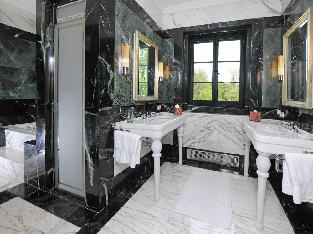 The primary bathroom has black marble walls that contrast the white sinks and white marble flooring. Image courtesy of Toptenrealestatedeals.com.