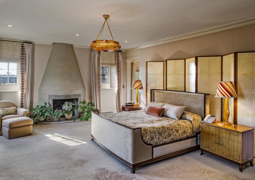This is the primary bedroom with a sleigh bed matching the beige tone of the walls. There is a fireplace on the side adorned with potted plants. Image courtesy of Toptenrealestatedeals.com.
