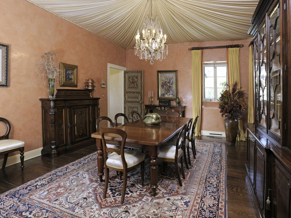 This formal dining room has a dark wooden dining table matched by the surrounding chairs and the cabinets on the walls. This is topped with a ceiling that is adorned with a linen cover and a chandelier in the middle. Image courtesy of Toptenrealestatedeals.com.
