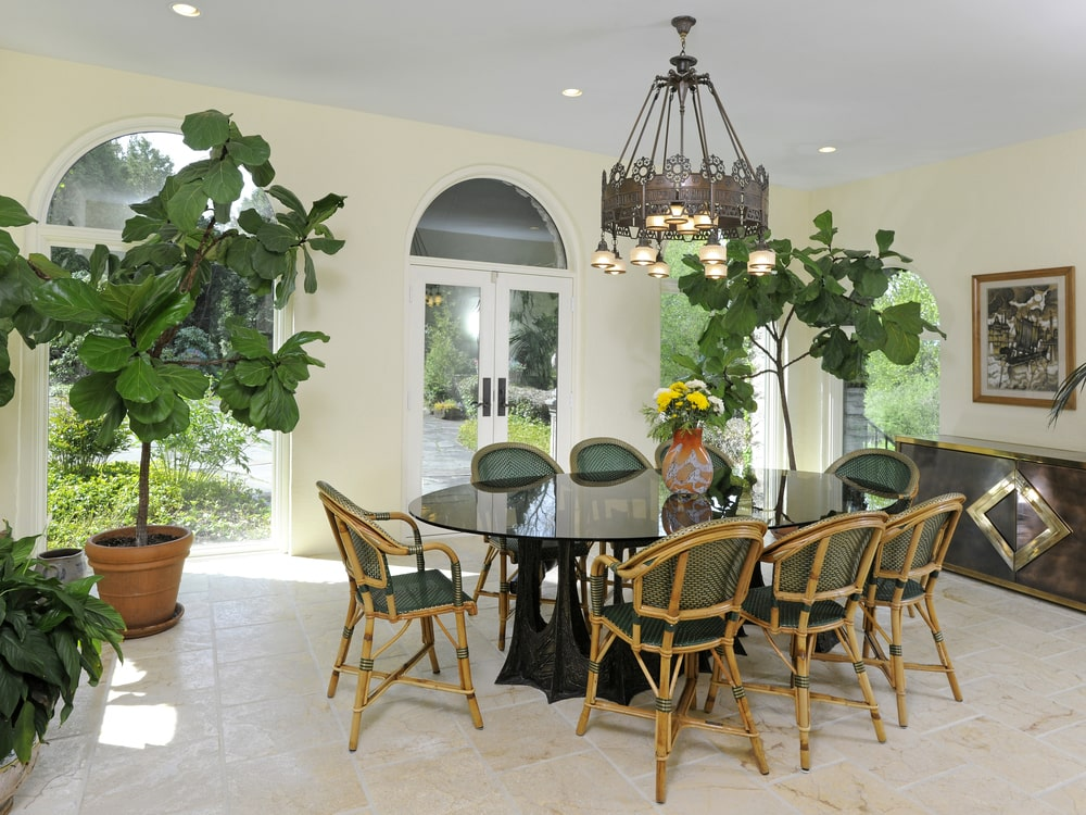 This patio dining area has a large elliptical black dining table surrounded by bamboo dining chairs and topped with a dark-toned chandelier hanging from the ceiling. Image courtesy of Toptenrealestatedeals.com.