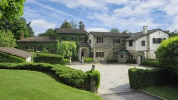 This is a view of the front of the house showcasing the stone walls and dark-tones roofs that stand out against the surrounding green landscaping filled with tall trees and thick shrubs. Image courtesy of Toptenrealestatedeals.com.
