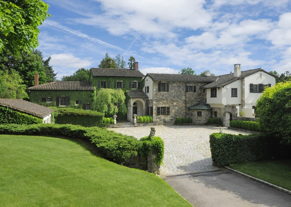 This is a view of the front of the house showcasing the stone walls and dark-tones roofs that stand out against the surrounding green landscaping filled with tall trees and thick shrubs.