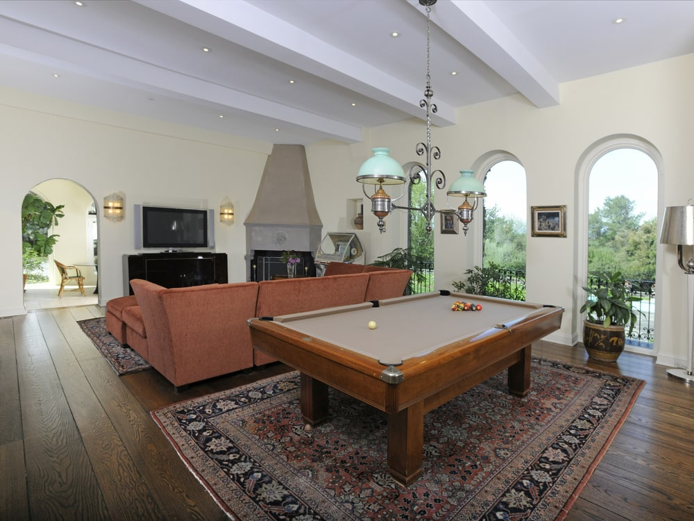 This is the game room with a brown sectional sofa on the side of the large pool table topped with a chandelier. Image courtesy of Toptenrealestatedeals.com.