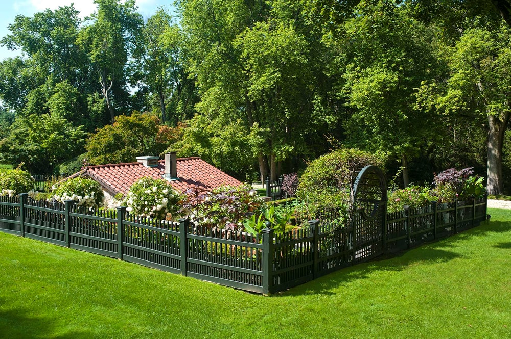 This is a look at the garden with colorful flowering shrubs and plants protected by wrought-iron fences. Image courtesy of Toptenrealestatedeals.com.