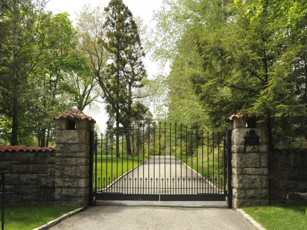 This is a look at the property from the vantage of the main gate. Here you can see two tall stone pillars supporting the wrought-iron main gate of the property. Image courtesy of Toptenrealestatedeals.com.