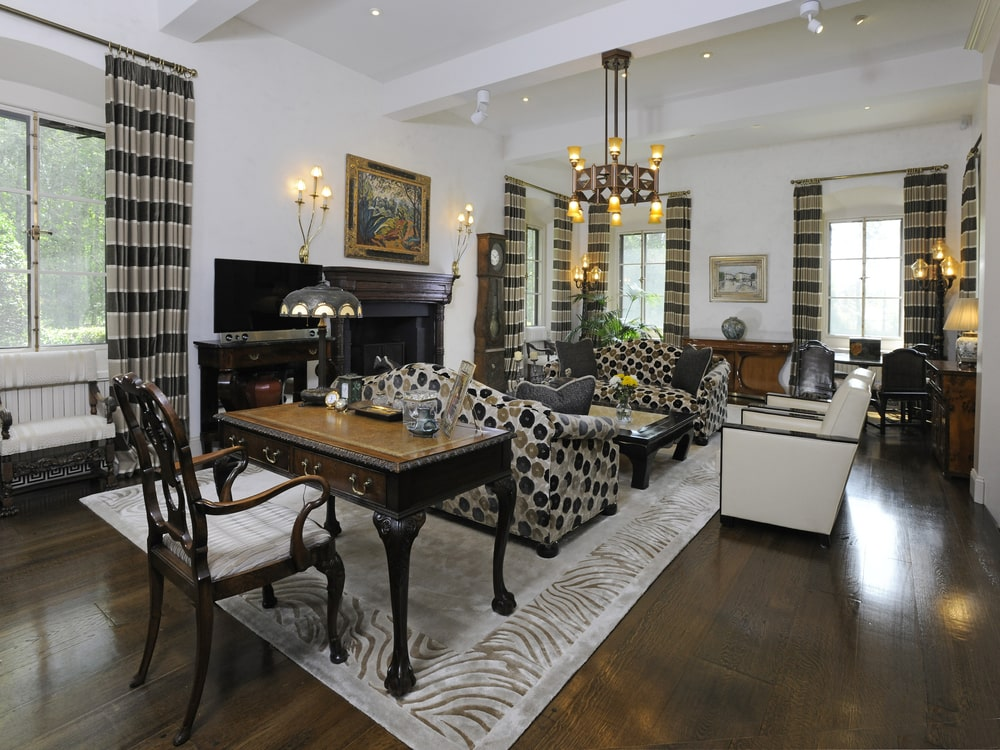 This is the living room with a pair of patterned sofas topped with a circular chandelier across from the black fireplace that is topped with a painting. Image courtesy of Toptenrealestatedeals.com.