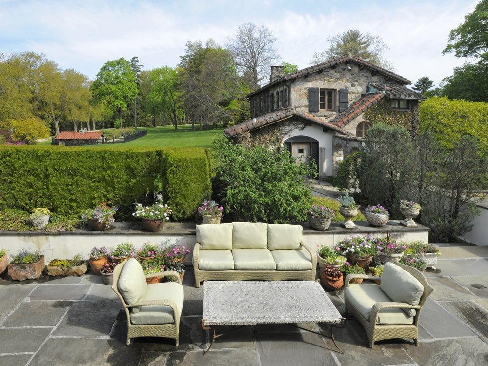 This is the outdoor patio that is fitted with a set of outdoor sofa and a coffee table. These are then complemented by the landscaping of shrub hedges and potted plants. Image courtesy of Toptenrealestatedeals.com.