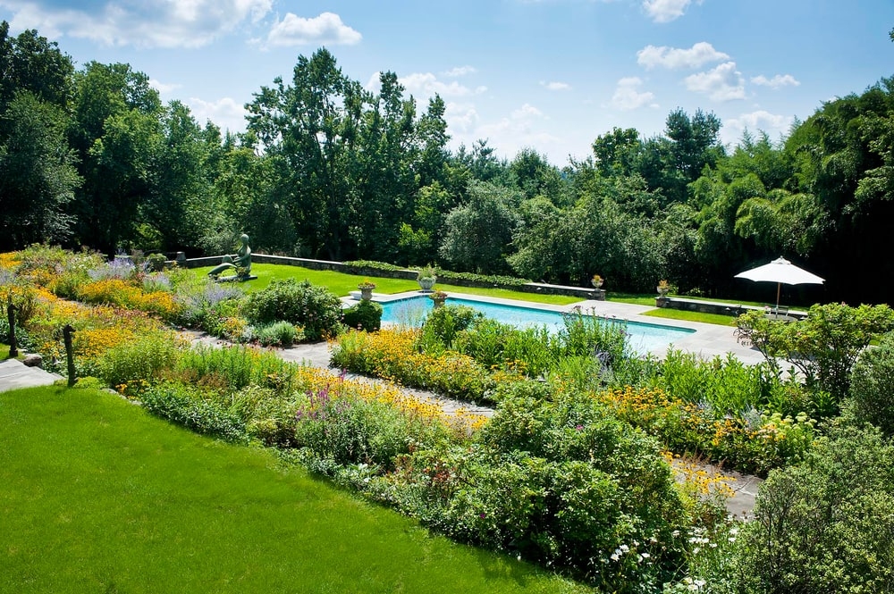 This is a look at the swimming pool from the vantage of the house exterior. You can see here the concrete walkway leading to it that is adorned on both sides with thick colorful shrubs. Image courtesy of Toptenrealestatedeals.com.