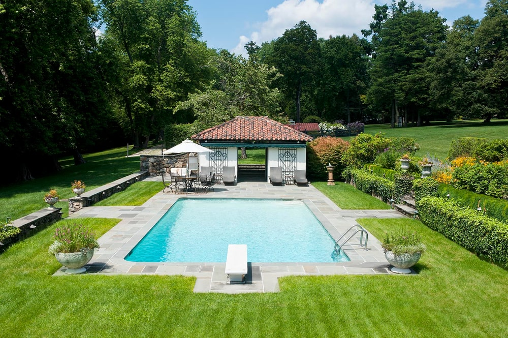 This is a closer look at the backyard swimming pool with a small pool house at the far side. This whole area is adorned by the surrounding landscape of shrubs, grass lawns and tall trees in the background. Image courtesy of Toptenrealestatedeals.com.