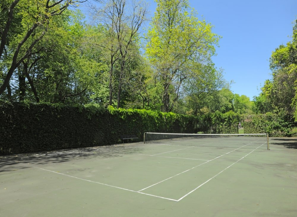 This is the professional-sized tennis court of the estate surrounded by tall hedges of shrubs and tall trees. Image courtesy of Toptenrealestatedeals.com.