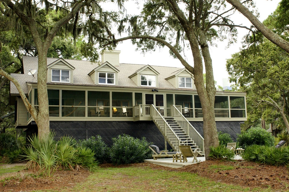 This is the front view of the house with light-toned exteriors, dormer windows and a large screened front porch. Image courtesy of Toptenrealestatedeals.com.