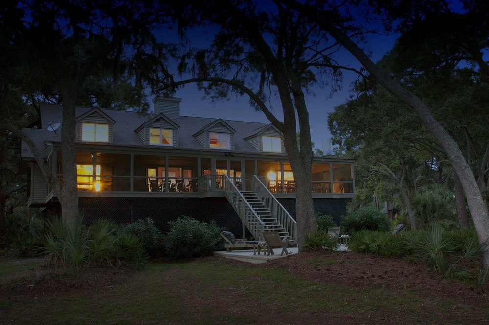 This is the nighttime view of the house featuring the warm glow of the interiors escaping through the dormer windows and screened front porch. Image courtesy of Toptenrealestatedeals.com.