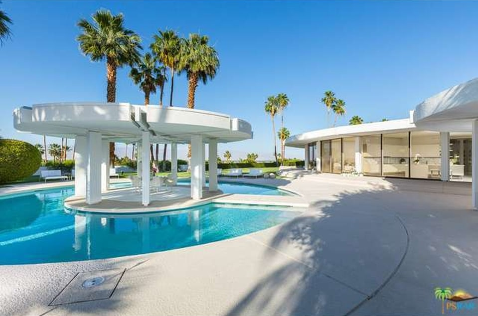 This is the back view of the house featuring the moat-style pool around a round island. You can also see here the glass walls of the main house. Image courtesy of Toptenrealestatedeals.com.