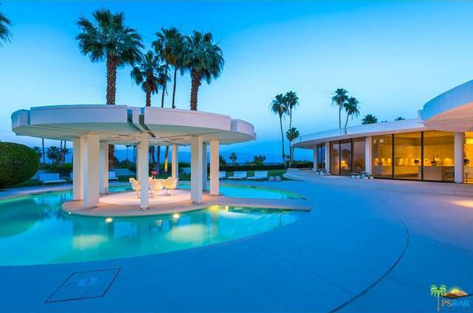 This is a nighttime view of the back of the house showcasing the outdoor lights that complement the pool and the covered island in the middle. You can also see here the warm glow of the glass walls. Image courtesy of Toptenrealestatedeals.com.