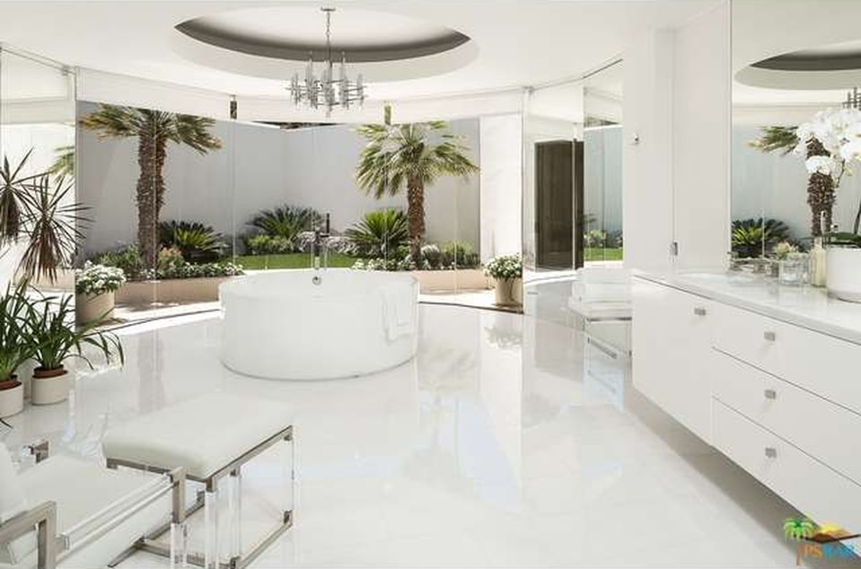 The bright white floor, walls, ceiling and freestanding bathtub of this bathroom are complemented by the green landscaping just outside the glass walls on the far side. Image courtesy of Toptenrealestatedeals.com.