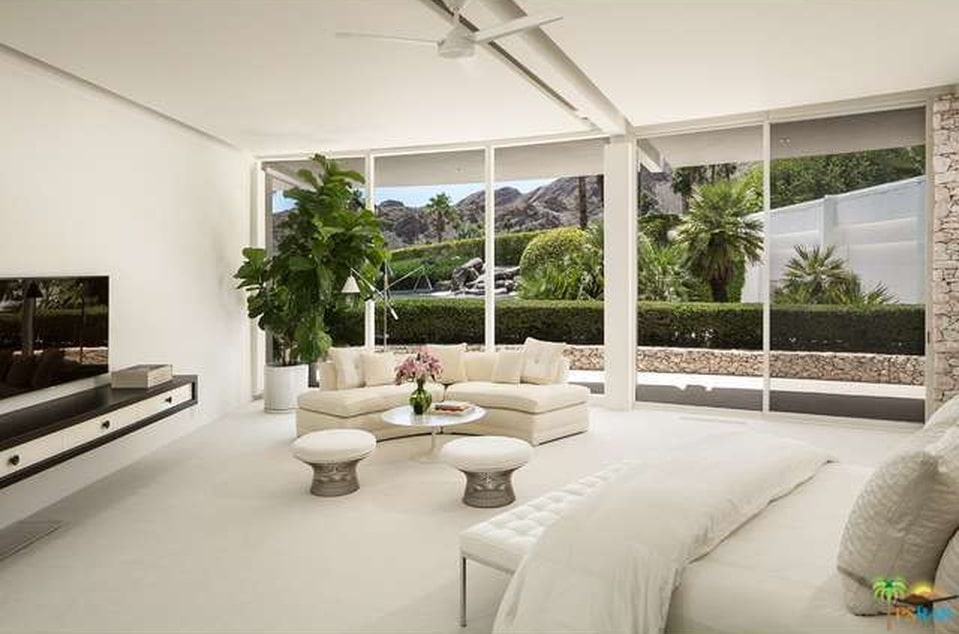 This is a bright and airy spacious bedroom with a beige bed, beige walls and ceiling. These are then complemented by the potted plant at the far corner that matches the landscape outside the glass wall. Image courtesy of Toptenrealestatedeals.com.