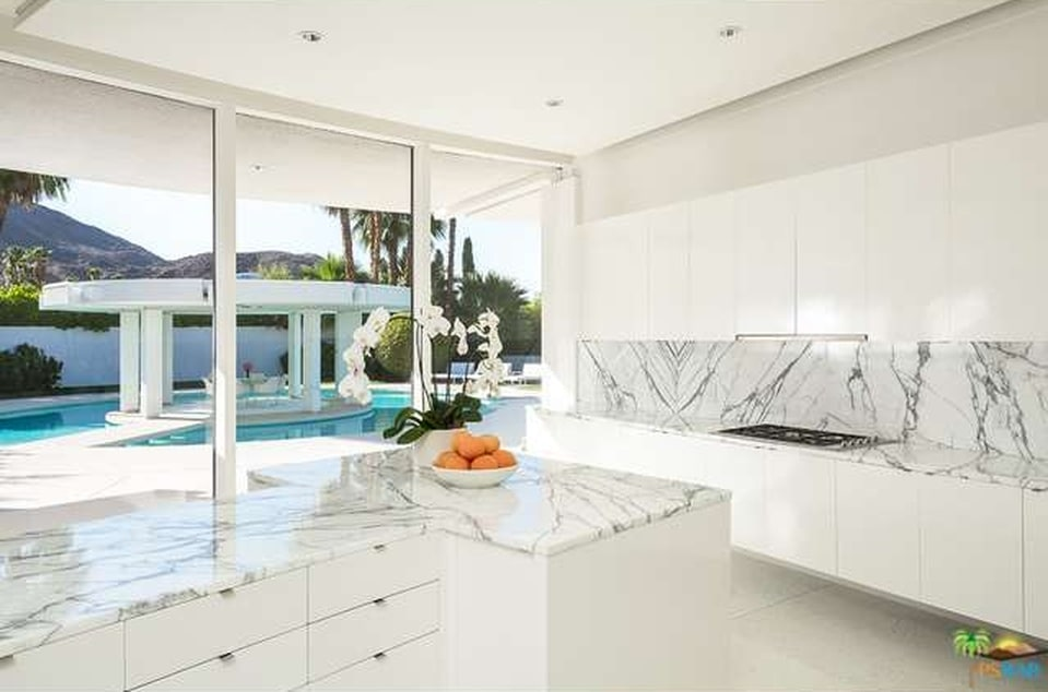 This is the kitchen that has bright cabinetry complemented by the white marble countertops and backsplash. Image courtesy of Toptenrealestatedeals.com.