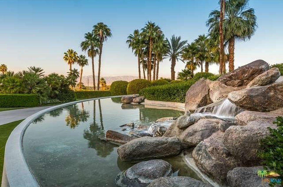This is a close look at the landscaping with a large stone waterfall water display and a background of tall palm trees. Image courtesy of Toptenrealestatedeals.com.