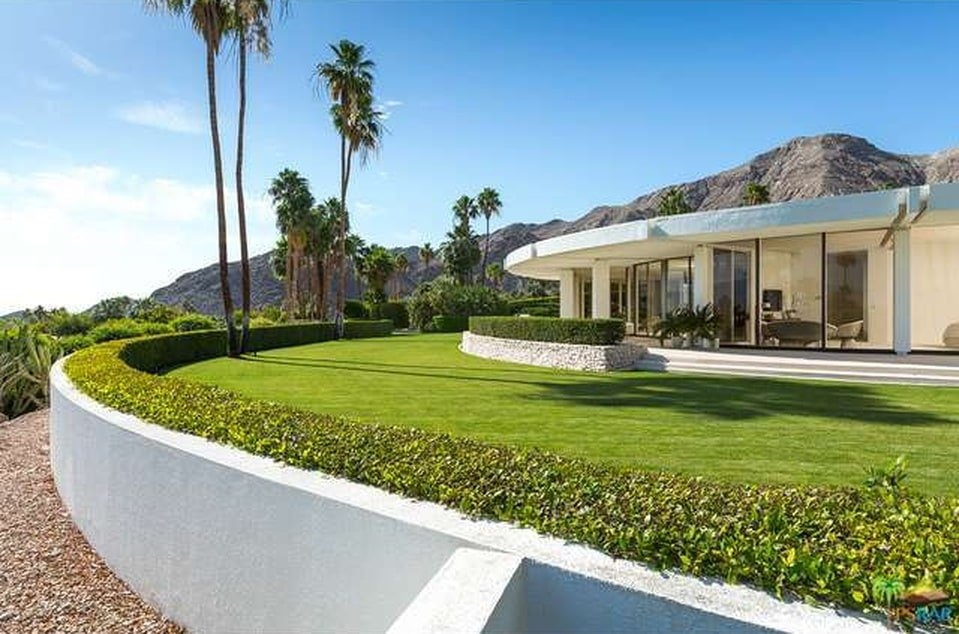 This is a look at the well-maintained grass lawn at the side of the house adorned with a hedge of shrubs and tall palm trees. These green elements pair well with the bright exteriors of the house. Image courtesy of Toptenrealestatedeals.com.