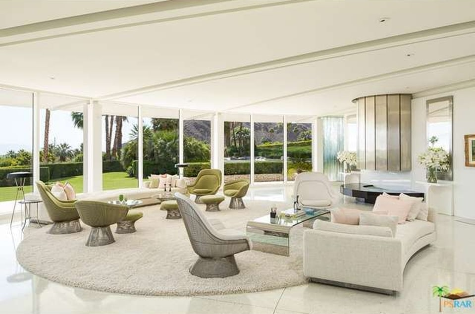 This is a look at the large open area of the living room illuminated by the curved wall of glass and warmed by the fireplace. Image courtesy of Toptenrealestatedeals.com.