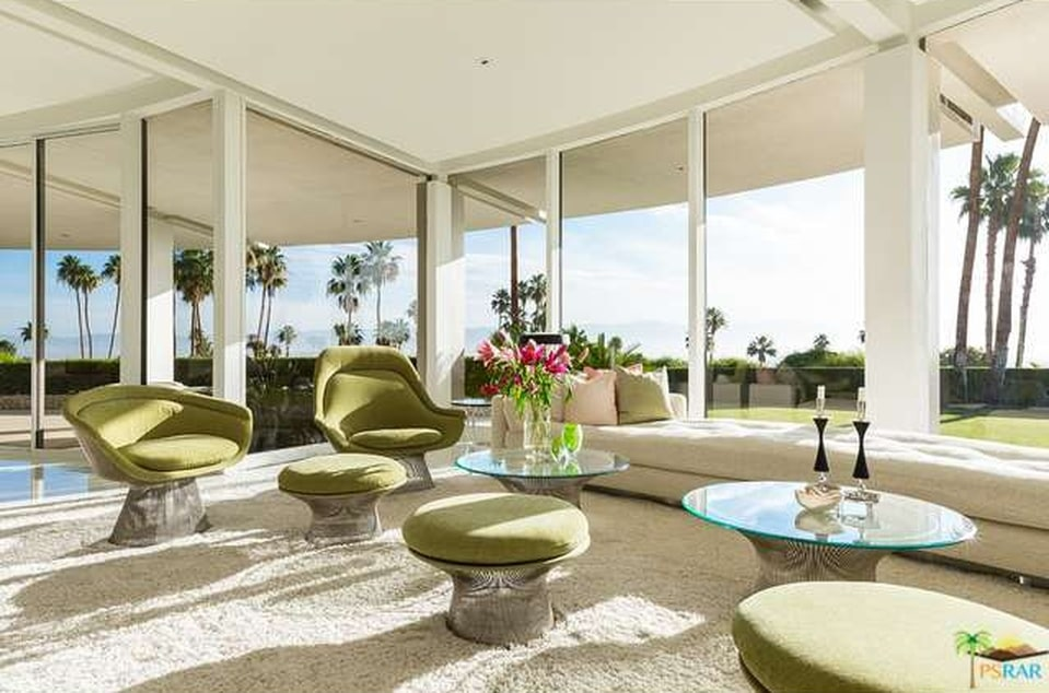 This is a closer look at the living room area just beside the glass wall. The bright beige tones of this area is complemented by the moss green cushions of the ottomans and armchairs. Image courtesy of Toptenrealestatedeals.com.